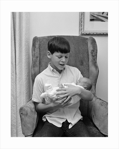 1960s pre-teen boy sitting in armchair holding infant newborn baby sibling by Corbis