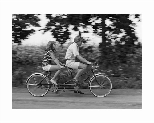 1970s teenage girl and boy riding bicycle built for two by Corbis