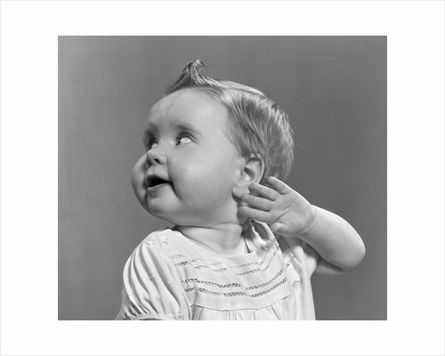 1940s 1950s close-up portrait of baby girl with curl on top of head looking to side with hand held up beside ear by Corbis
