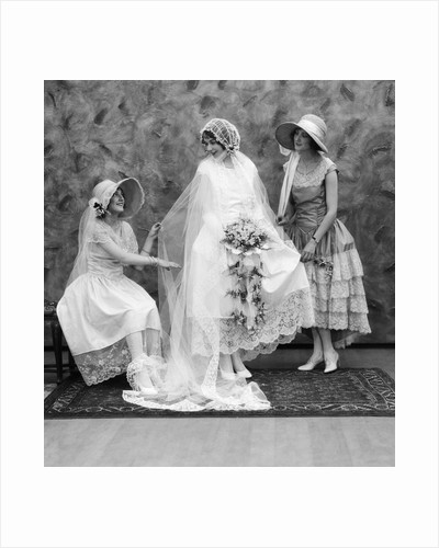 1900 1910s bride with one bridesmaid on either side helping fix her wedding dress by Corbis