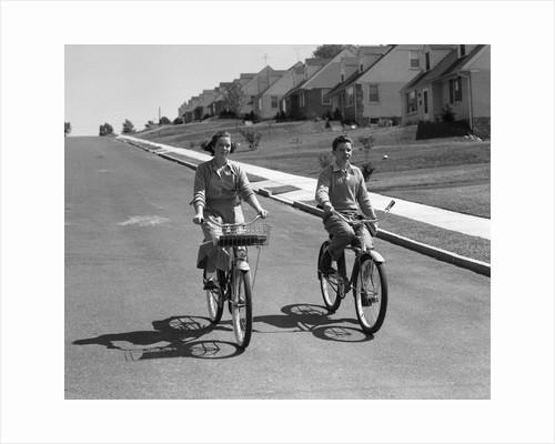 1950s teen boy girl couple riding bikes down residential street by Corbis