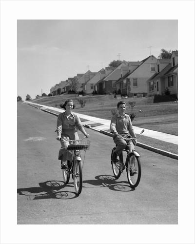 1950s teen boy girl riding bikes suburban neighborhood street by Corbis