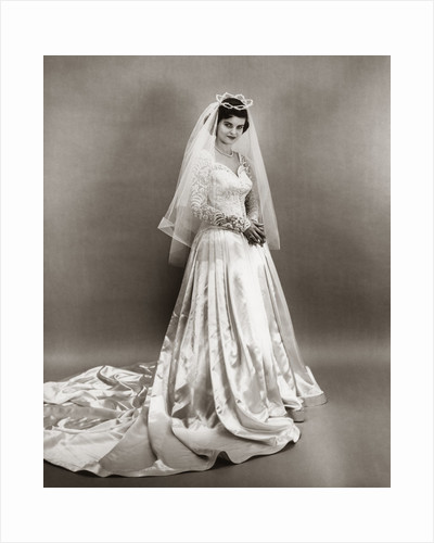 1950s full length portrait bride standing wearing satin and lace wedding gown veil and tiara looking at camera by Corbis