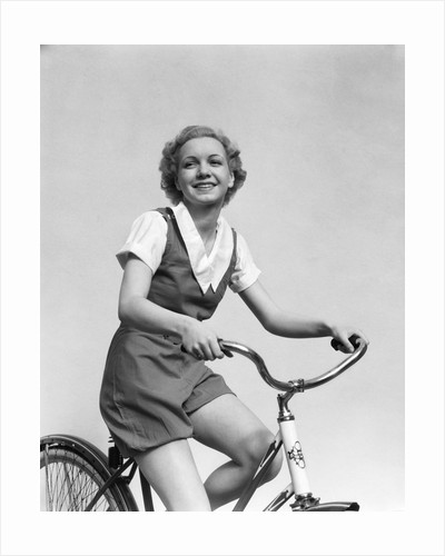 1930s smiling blonde woman riding bicycle looking at camera by Corbis