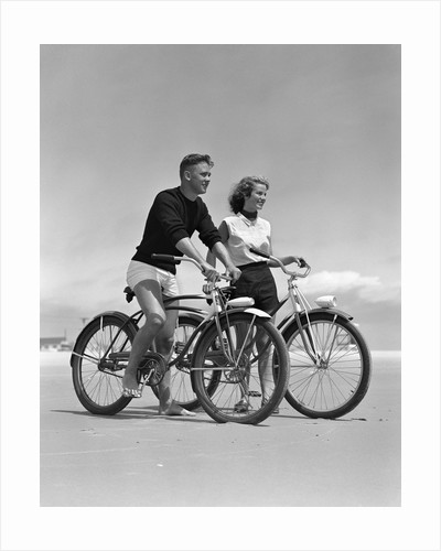 1950s teenage boy and girl with bikes on the beach by Corbis