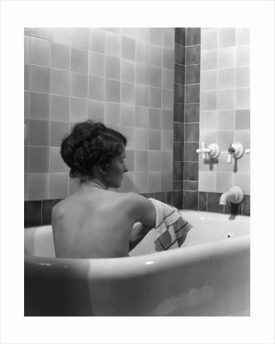 1920s 1930s young brunette woman sitting in luxury bathtub taking a bath by Corbis