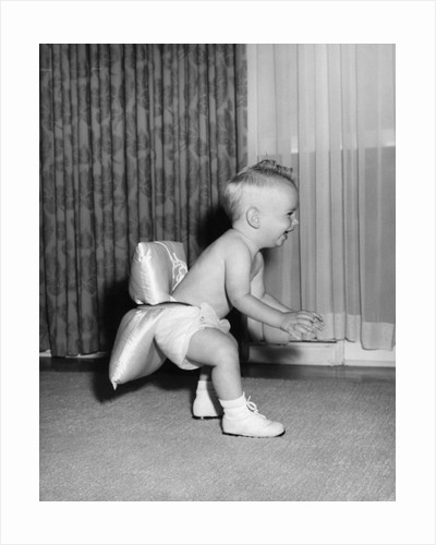 1950s laughing baby in diaper and shoes learning to walk with a pillow tied to his rear end by Corbis