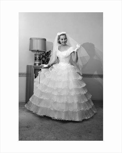 1950s 1960s bride in full gown veil & white gloves standing in room with open door by Corbis