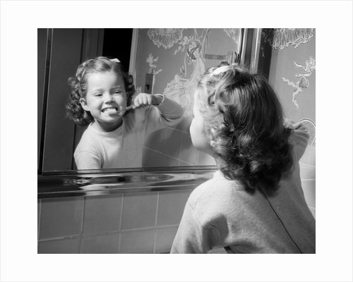 1950s girl looking in bathroom mirror brushing teeth by Corbis