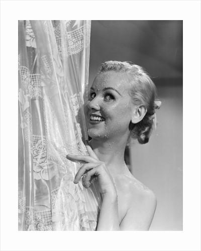 1950s portrait of wet blonde peeking around shower curtain by Corbis