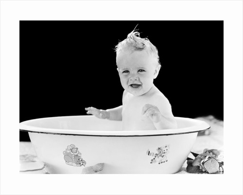 1930s 1940s smiling happy baby sitting in enameled tin bathtub by Corbis