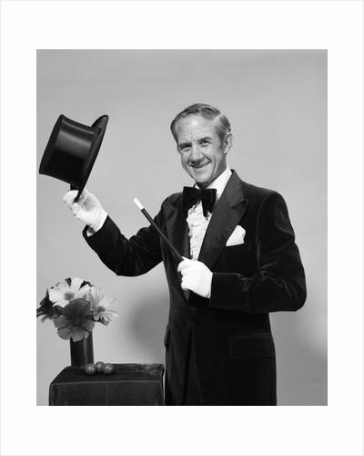 1970s smiling man magician wearing velvet tuxedo white gloves pointing magic wand at top hat looking at camera by Corbis