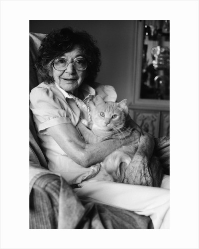 1980s elderly senior woman wear glasses holding tabby cat in her arms lap pet geriatric companion old age therapy animal looking at camera by Corbis