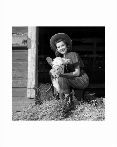 Girl posing with calf in straw filled stall in barn by Corbis
