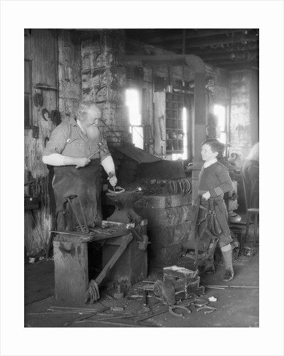 1930s elderly blacksmith with hammer at anvil as young boy holding harness looks on smiling by Corbis