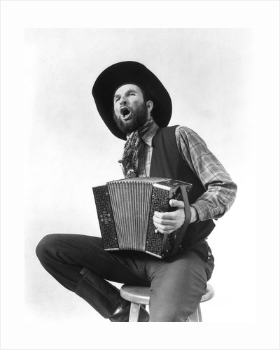 1930s cowboy playing accordion & singing by Corbis