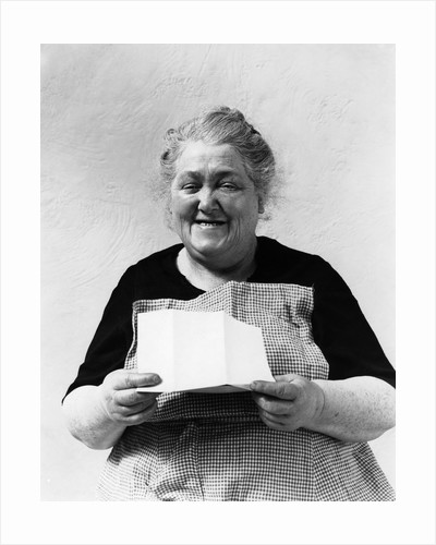 1930s 1940s elderly character woman smiling reading letter wearing apron looking at camera by Corbis