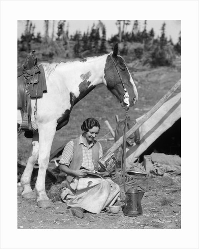 1920s 1930s woman sitting outside of tent next to pinto horse pouring syrup from tin onto pancakes wearing vest and chaps glacier park by Corbis