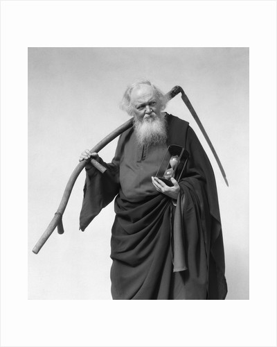 1930s elderly white-bearded man in long robe carrying scythe and hourglass by Corbis