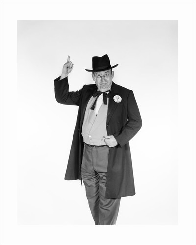 1950s 1960s man wearing old-time politician frock coat with campaign pin back button pointing index finger in air looking at camera by Corbis