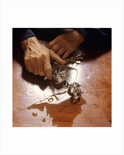 1980s hand holding spilled alcoholic drink on bar with keys in other hand by Corbis