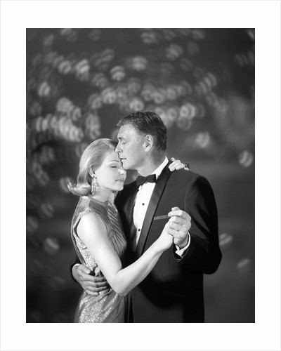 1960s couple woman in evening dress and man in tuxedo slow dancing by Corbis