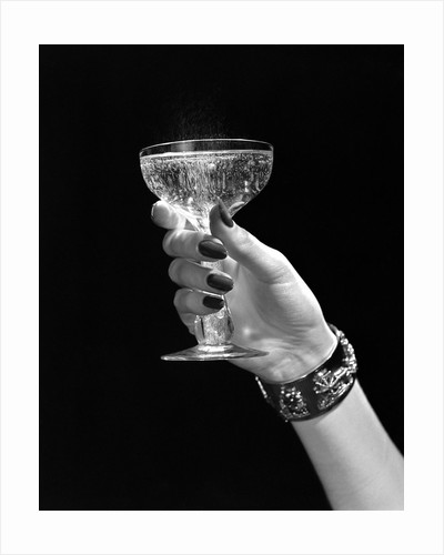 1930s 1940s 1950s woman hand ornate metal bracelet holding up new year toast glass of champagne against black background by Corbis