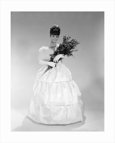 1960s pretty young woman in evening dress at beauty pageant wearing fur stole and tiara holding bouquet of roses looking at camera by Corbis