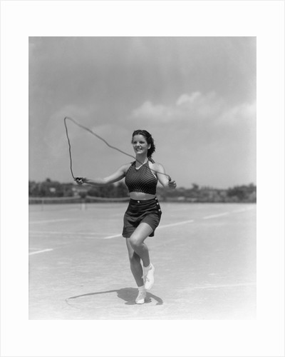 1930s woman jumping rope exercise outdoors wearing polka dot halter top and shorts by Corbis