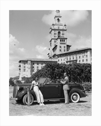 1930s couple with golf clubs standing by a car in front of the biltmore hotel miami florida by Corbis