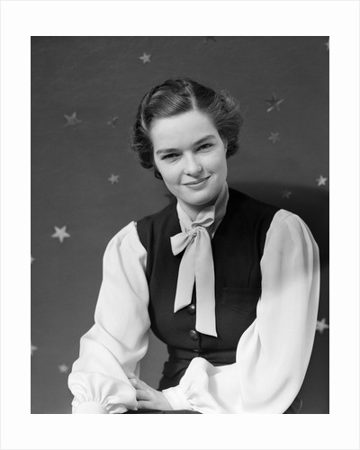 1930s woman portrait smiling star printed backdrop wearing vest bow collar looking at camera by Corbis