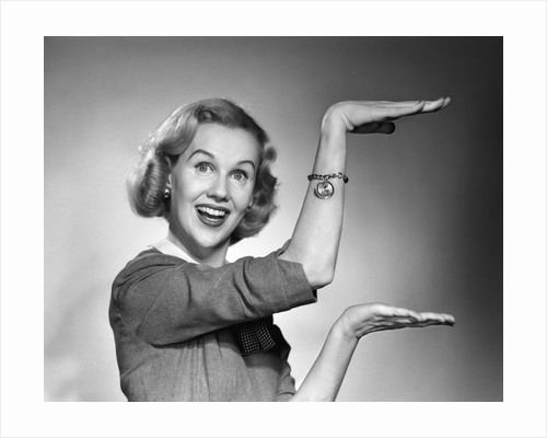 1950s 1960s happy smiling blond woman gesturing with hands showing size of something looking at camera by Corbis