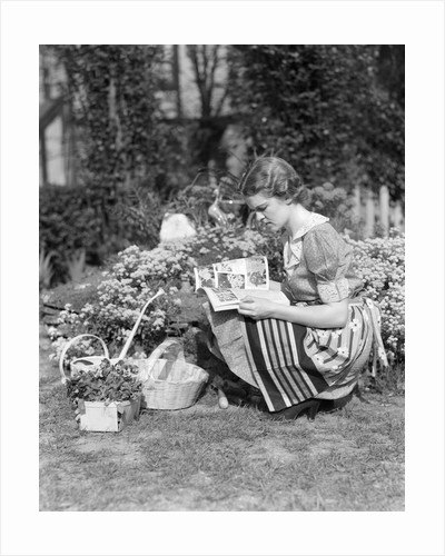 1930s 1940s woman dressed in print dress striped apron kneeling in flowers garden reading a gardening manual by Corbis