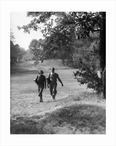 1930s couple man woman each carrying a golf bag walking down the fairway of the golf