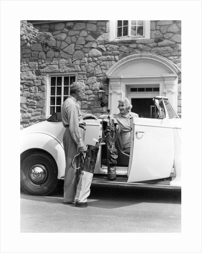 1940s senior retired couple loading golf clubs into white convertible car in front stone house by Corbis