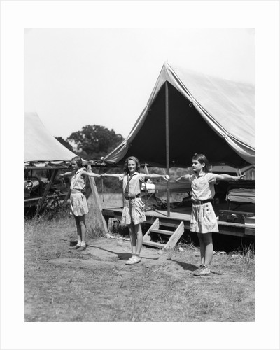 1930s three teen girls doing exercise in a row with arms extended by tent summer camp by Corbis