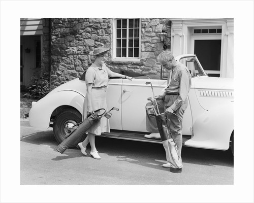 1930s 1940s senior couple putting golf clubs in convertible car by stone house by Corbis