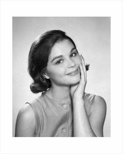 1960s smiling brunette young woman hand to cheek facial expression gesture looking at camera by Corbis