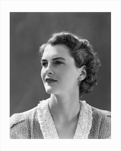 1940s profile portrait brunette woman wearing print dress with lace collar by Corbis