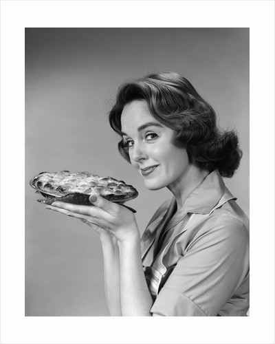 1950s 1960s woman smiling holding freshly baked pie looking at camera by Corbis