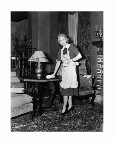 1940s blonde woman housewife maid wearing apron cleaning polishing wooden end table in ornate living room by Corbis