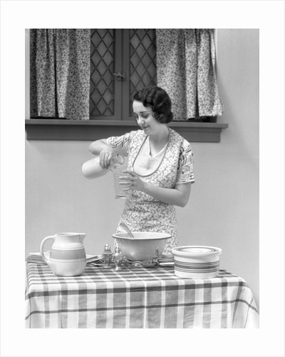 1920s 1930s woman pouring milk into measuring cup by Corbis