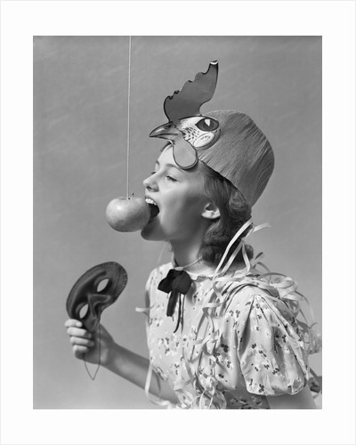 1930s 1940s girl bobbing for apple dangling on a string wearing party hat and holding eye mask by Corbis