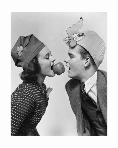 1940s couple teen boy and girl wearing party hats bobbing for an apple on a string by Corbis