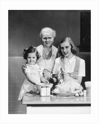1940s 1950s mother daughter grandmother stuffing turkey by Corbis