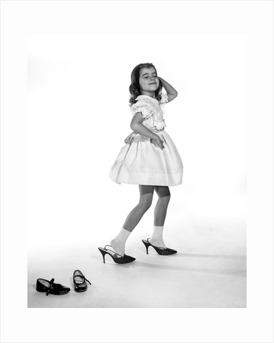 1960s girl making glamour pose having stepped out of her shoes into her mothers adult high heels by Corbis