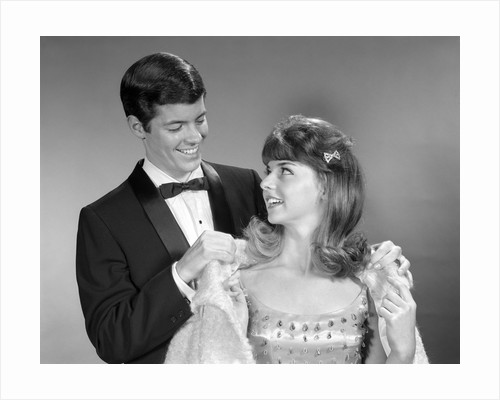 1960s teen couple formally dressed boy helping girl on with coat to go to prom by Corbis