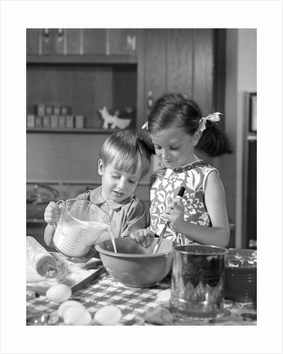 1960s two children boy girl bowl mixing pouring milk in kitchen by Corbis