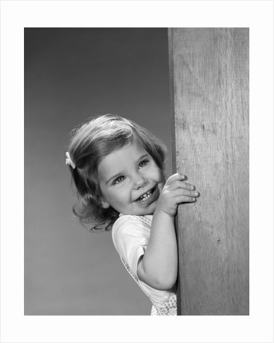1960s child little girl smiling peeking around corner by Corbis