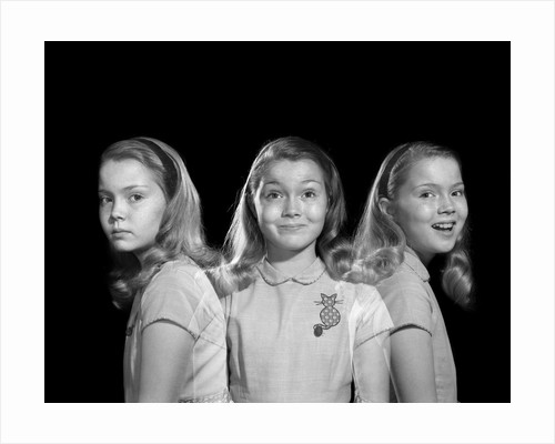 1950s 1960s multiple exposure girl going from happy to sad three facial expressions looking at camera by Corbis